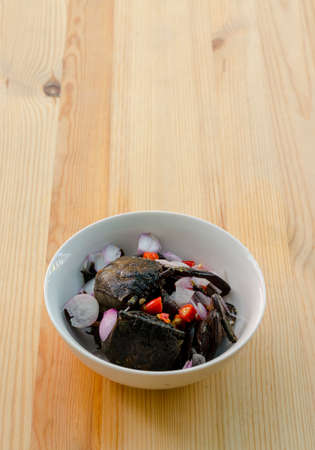 Small black crab sour salad on wooden background, Thai traditional food