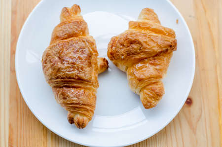Croissant, Breaded bread on a wooden tra and white dishy delicious breakfast. Stock Photo