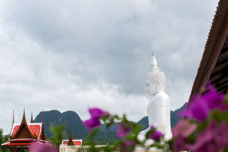 The white buddha statue in public place of Thai temple on the blue sky