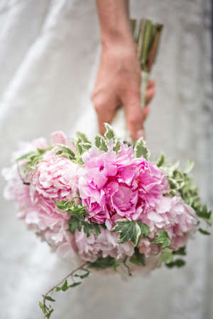 hand of the bride with a beautiful wedding bouquet of peonies