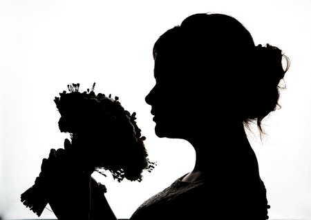 Young bride silhouette  with wedding bouquet on a white background Reklamní fotografie