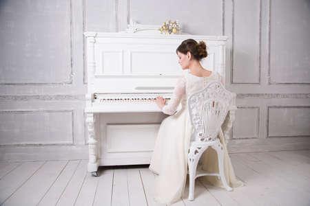 後方に座っていると、ピアノを弾く白いウェディング ドレスの若い花嫁 写真素材 - 89992829
