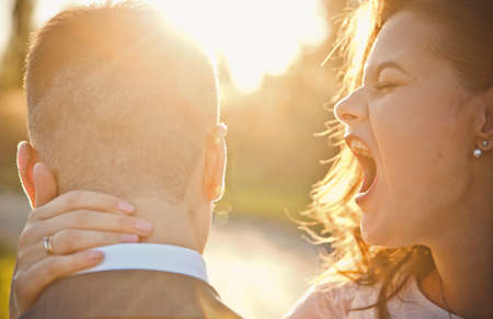 A young bride laughs and yells in the ear of the groom