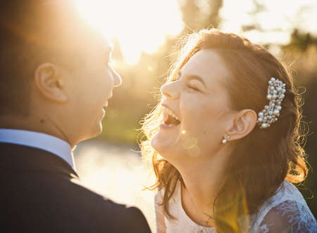 a young bride and groom laughs and yells face to face Stock Photo