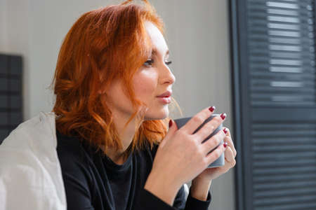 Charming young woman with red hair, drinking coffe wrapped at blanked. Cheerful time, excited emotion,