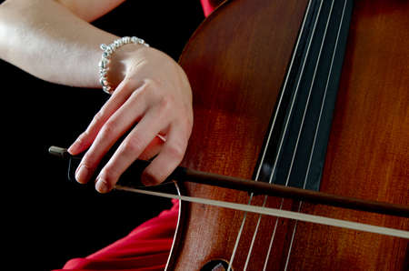 Closeup of a female hand moving the bow of a cello photo