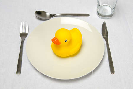 A rubber duck sitting on a plate ready for dinner. Good for cooking instructions for children or other funny concepts photo