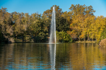 water jet: Autumn colors reflecting on a lake with a water jet and a blue sky