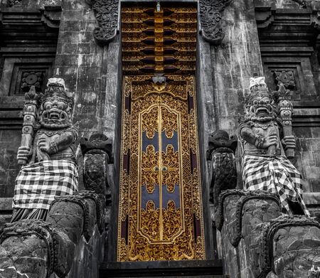 large doors: Golden doors of a temple protected by two statues with large teeth Editorial