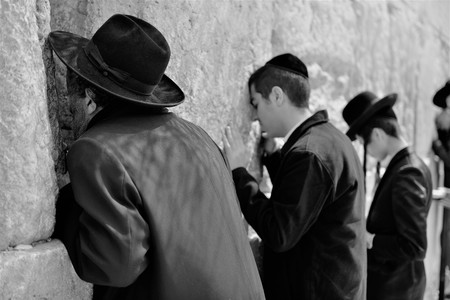 Orthodox hassidic religious jews dressed in black traditional outfit pray at the wailing wall during the high holidays in jerusalem israel