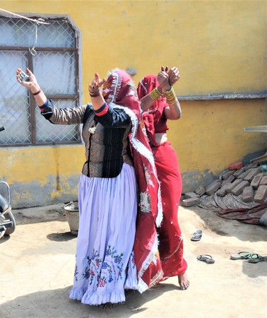 Women celebrating Holi holidays in India with traditional indian costumes