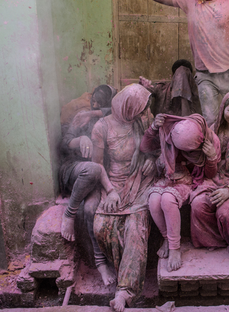 People sitting on the street in the villages of Barsa and Mathura India during the holi festivals days and are covered with powder in all different colors especially pink and red Foto de archivo