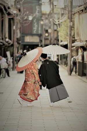 A japanese couple on their wedding day dressed up in traditional kimono taking photo shots in kyoto