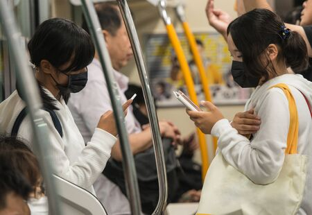 Young Japanese school girl dressed in school uniform and surgical masks on their face texting with their mobile phone in the subway underground on the way to school