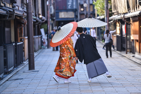 Younge japanese  couple dressed in kimono traditional costume on their marriage day taking some photo shots