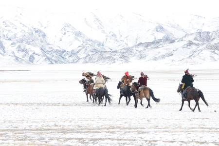 Mongolian horse riders dash between the snowy mountains in the winter of mongolia during the golden eagle festival Stockfoto