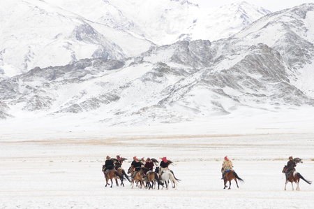 Mongolian horse riders dash between the snowy mountains in the winter of mongolia during the golden eagle festival Reklamní fotografie