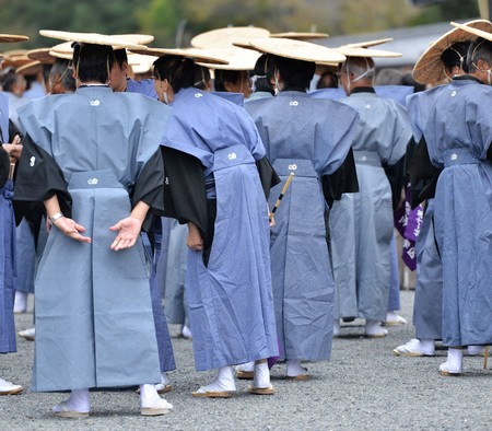 Traditional blue japanese costumes with roond flat hats during jidai matsuri festival in kyoto