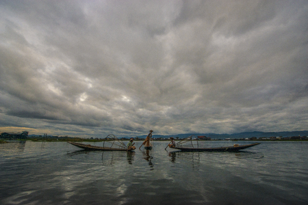 Myanmar`s balancing fishermen are trained skilled to stand on one leg, and paddle with the other while hunting carp fish in sunset