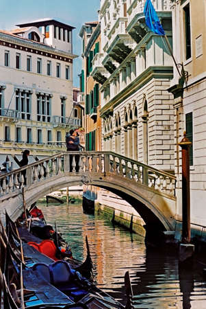 A quiet backwater of Venice with a young couple on the bridge.