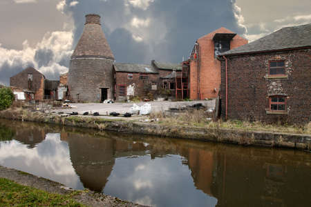 An abandoned pottery factory stands allongside the Trent and Mersey canal that in bygone times transported it's products. Stock Photo - 7319938