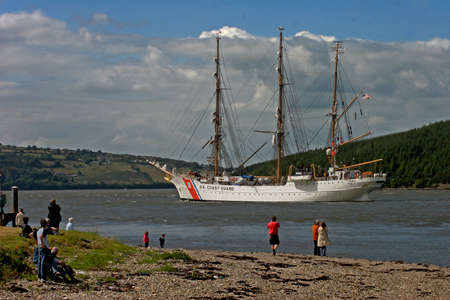 tall ship: Onlookers watch as the tall ship US COAST GUARD travels up the Suir Estuary towards Waterford in the Irish Republic.