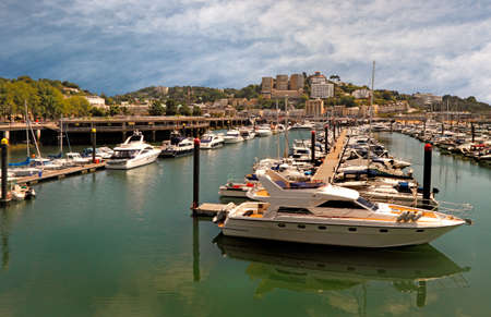 prevailing: The marina at Torquay in Devon, England is well sheltered from prevailing west winds and has berths for around four hundred and fifty boats  Stock Photo