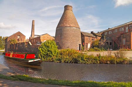 A canal narrow boat passes an abandoned pottery factory on the Trent and Mersey canal at Longport, Stoke on Trent in England.