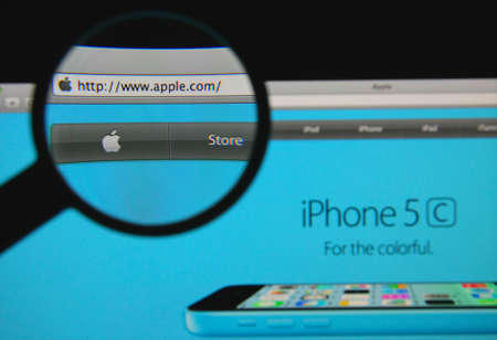 iphone5: LISBON - JANUARY 21, 2014: Photo of Apple homepage on a monitor screen through a magnifying glass.