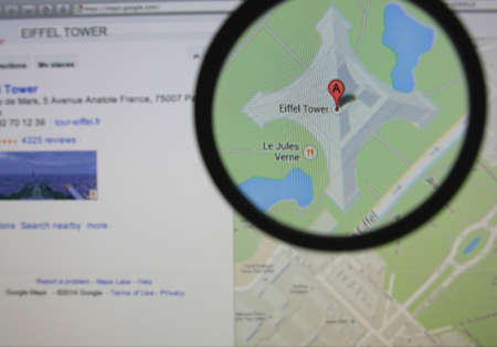LISSABON - 23 januari 2014: Foto van Google Maps peilen van de Eiffeltoren op een beeldscherm door een vergrootglas.