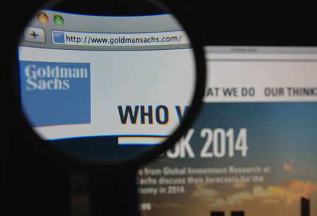 LISBON - JANUARY 22, 2014: Photo of Goldman Sachs homepage on a monitor screen through a magnifying glass.