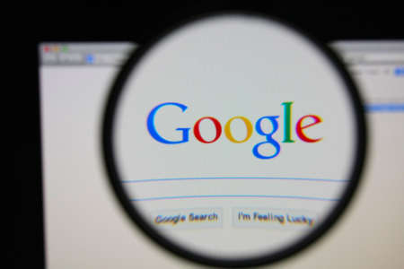 LISBON - JANUARY 22, 2014: Photo of Google homepage on a monitor screen through a magnifying glass. 報道画像