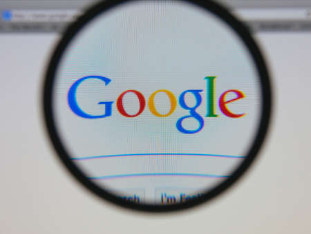 google: LISBON - JANUARY 23, 2014: Photo of Google homepage on a monitor screen through a magnifying glass.