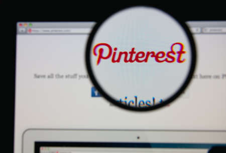 pinterest: LISBON - JANUARY 20, 2014: Photo of Pinterest homepage on a monitor screen through a magnifying glass. Editorial
