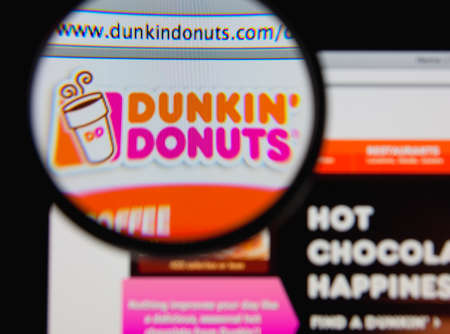 LISBON - JANUARY 20, 2014: Photo of Dunkin Donuts homepage on a monitor screen through a magnifying glass.