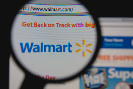 LISBON - JANUARY 23, 2014: Photo of Walmart homepage on a monitor screen through a magnifying glass.