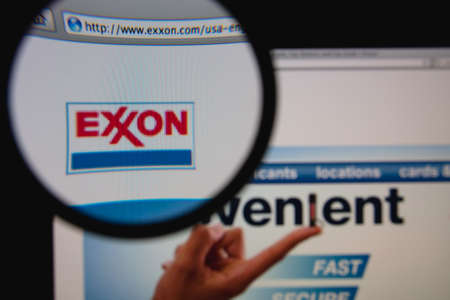 LISBON - JANUARY 23, 2014: Photo of Exxon homepage on a monitor screen through a magnifying glass.