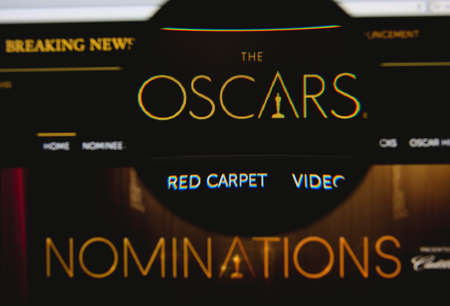 nominations: LISBON - JANUARY 23, 2014: Photo of the Academy Awards homepage on a monitor screen through a magnifying glass.