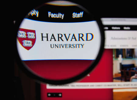 ivy league: LISBON - JANUARY 25, 2014: Photo of Harvard University homepage on a monitor screen through a magnifying glass.