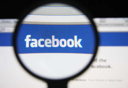 web scam: LISBON - DECEMBER 20, 2013: Photo of Facebook homepage on a monitor screen through a magnifying glass.