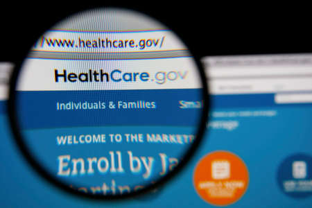 obama care: LISBON - JANUARY 14, 2014: Photo of HealthCare.gov homepage on a monitor screen through a magnifying glass.