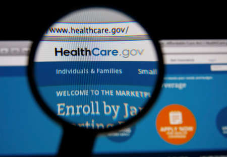 heathcare: LISBON - JANUARY 14, 2014: Photo of HealthCare.gov homepage on a monitor screen through a magnifying glass.
