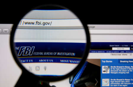 federal: LISBON - JANUARY 14, 2014: Photo of FBI homepage on a monitor screen through a magnifying glass.