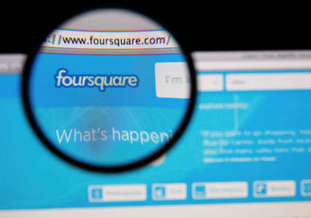 foursquare: LISBON - JANUARY 20, 2014: Photo of Foursquare homepage on a monitor screen through a magnifying glass.