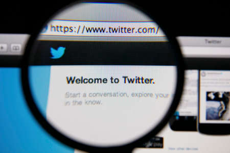 twitter: LISBON - JANUARY 14, 2014: Photo of Twitter homepage on a monitor screen through a magnifying glass.
