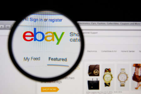 LISBON - JANUARY 14, 2014: Photo of Ebay homepage on a monitor screen through a magnifying glass.