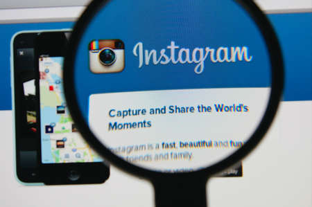 LISBON - JANUARY 22, 2014: Photo of Instagram homepage on a monitor screen through a magnifying glass. 報道画像