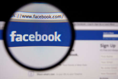 social web sites: LISBON - JANUARY 14, 2014: Photo of Facebook homepage on a monitor screen through a magnifying glass.