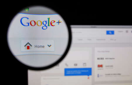 LISBON - JANUARY 14, 2014: Photo of Google+ homepage on a monitor screen through a magnifying glass. 報道画像