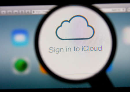 icloud: LISBON, PORTUGAL - FEBRUARY 8, 2014: Photo of Icloud homepage on a monitor screen through a magnifying glass.